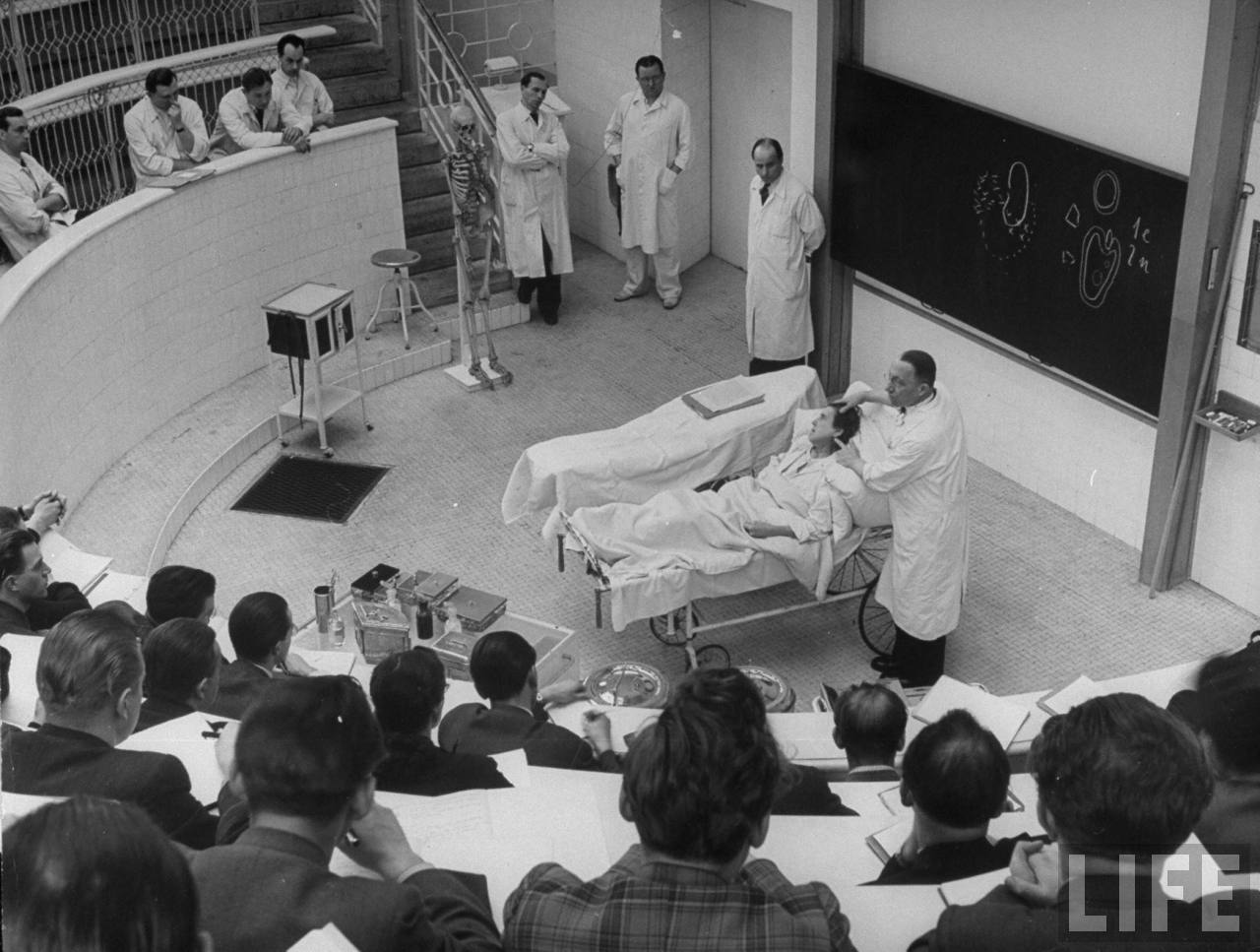 Brain surgeon Arnold Jirasek describing technique of operating on woman with a severely abscessed jaw to medical students from Charles University in amphitheater of his Clinic of Surgery.