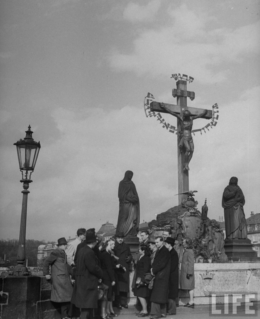 Charles University history class studying crucifix on historic Charles Bridge.