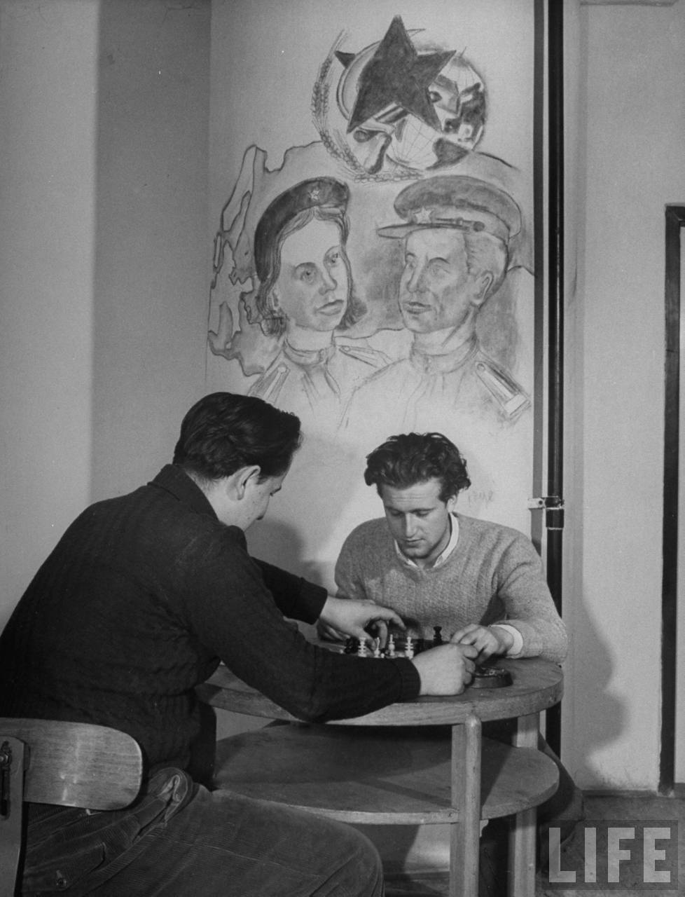 Two Czech students playing chess under student artwork on wall of room in the Marshal Tito Hall at Charles University.
